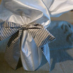 Bottle Wraps - sq of fabric with sash tied in a bow.